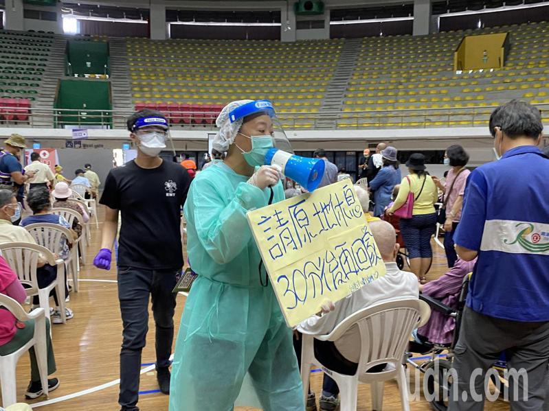 衛生人員手拿紙板及大聲公,提醒長輩施打完原地休息30分鐘觀察。記者尤聰光/攝影