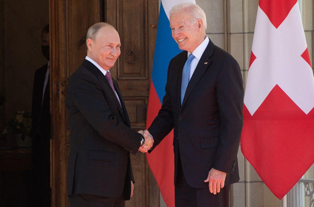 俄國總統普亭(左)與美國總統拜登(右)在峰會舉行前握手。法新社