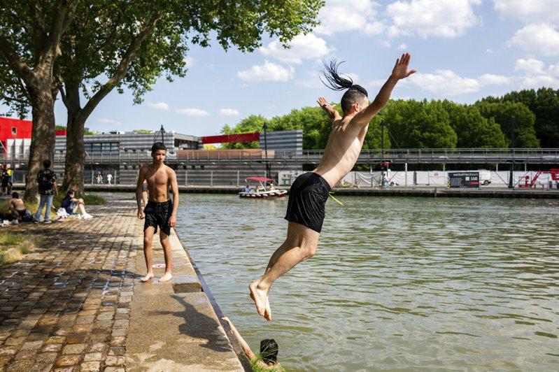 圖為巴黎高溫,青年脫光上身跳入烏爾克運河情形。美聯社