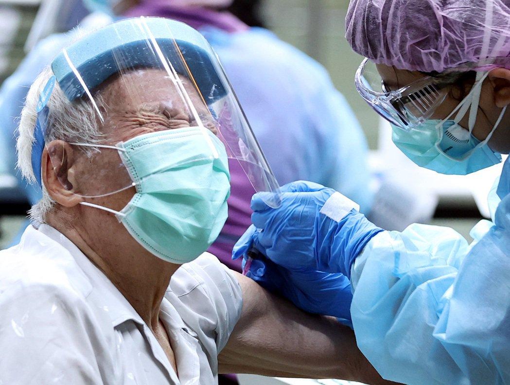 戴著面罩的老先生接種疫苗時露出痛苦表情,銀髮族為現階段接種重點對象,指揮中心希望...