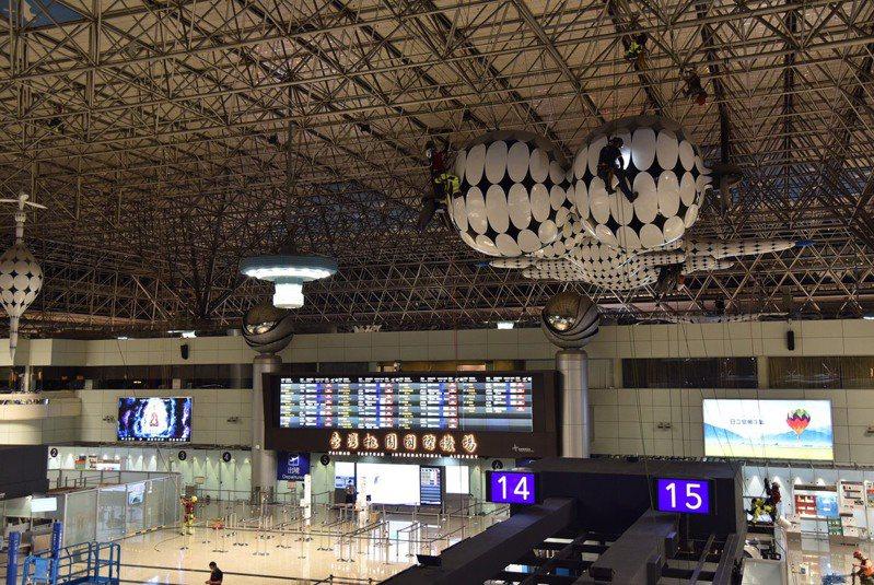 機場公司近日在夜間派出十位「蜘蛛人」,以繩索懸掛方式徹底清潔消毒第二航廈出境大廳大型公共藝術作品。圖/桃園機場公司提供