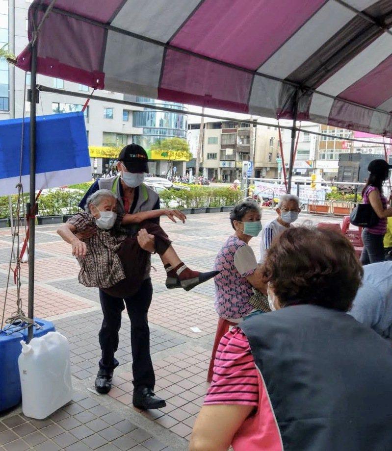台南市東區區公所主秘陳俊達今天在東區衛生所前抱著老人進入打疫苗,被現場民眾拍下照片。圖/讀者提供