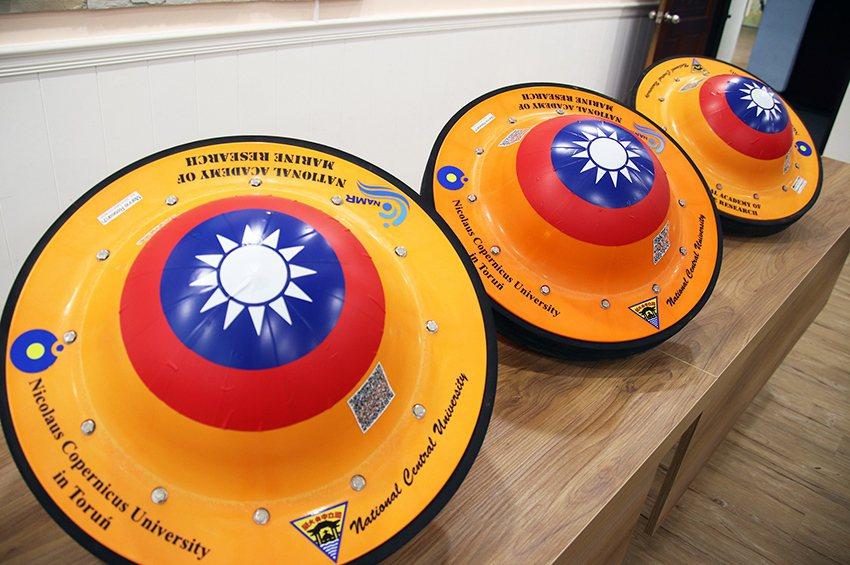 外觀狀似「飛碟」的海洋浮球,中間印有國旗,週邊印有國立中央大學、波蘭哥白尼大學和...