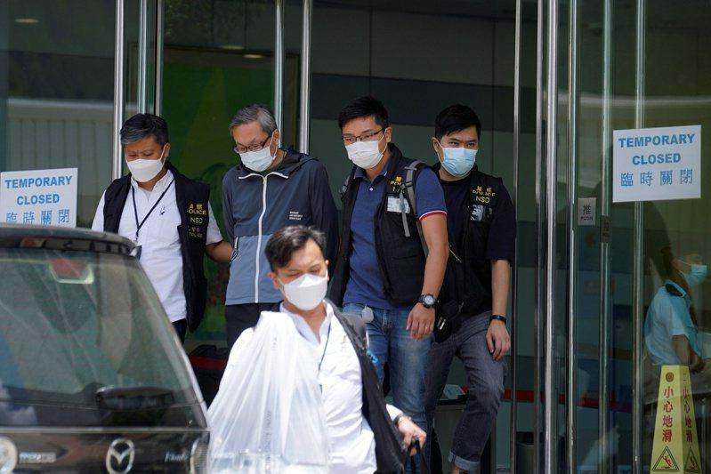 港警押著壹傳媒行政總裁張劍虹(左二)到蘋果日報大樓協助搜查後離開。(路透)