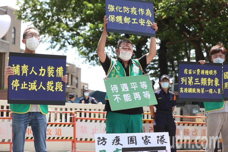 台灣郵政產業工會上午舉辦「共體時艱一場空 怒退獎章首日封」,工會成員舉牌表達憤怒...