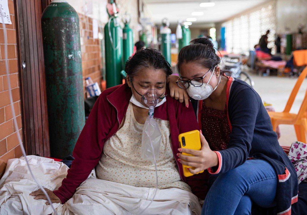 秘魯伊基托斯去年5月一名確診婦人在醫院靠著吸氧對抗病魔。(法新社)