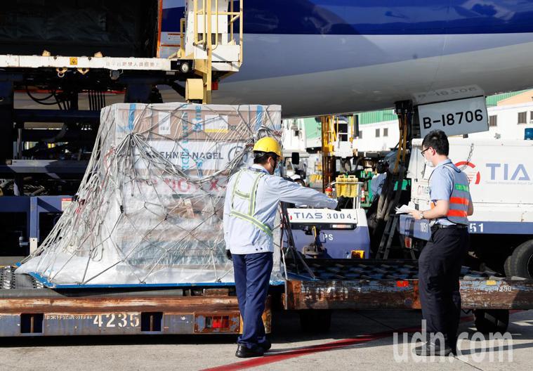 我國訂購的第二批24萬劑莫德納疫苗下午抵達桃園機場,疫苗卸下後,由海關人員在機邊...