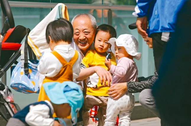 圖為北京一名年長者與孩童在玩耍。照片/美聯社
