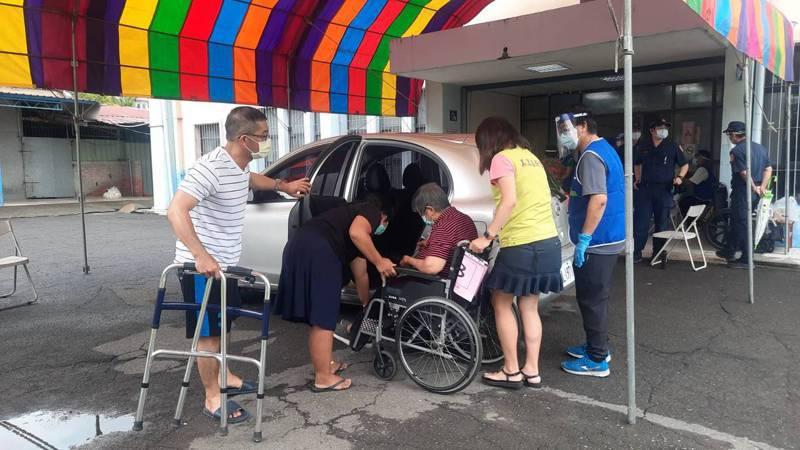 高雄市美濃國中大禮堂的疫苗施打站工作人員協助坐輪椅長輩下車。記者陳玫伶/攝影