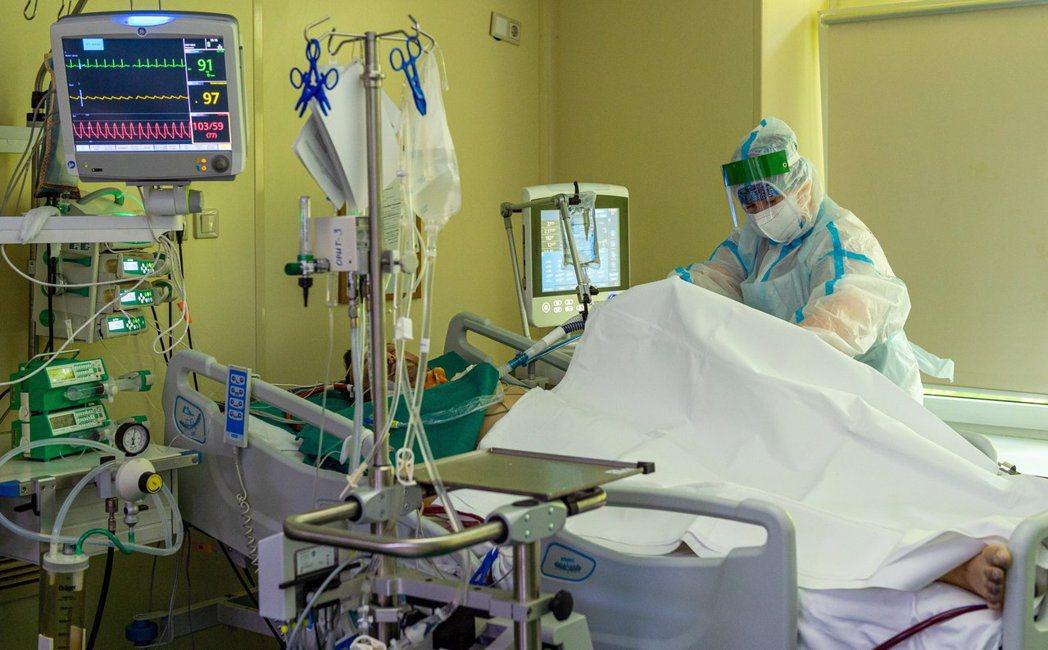 俄國莫斯科第52號市立醫院醫護人員17日正治療一名確診病患。美聯社
