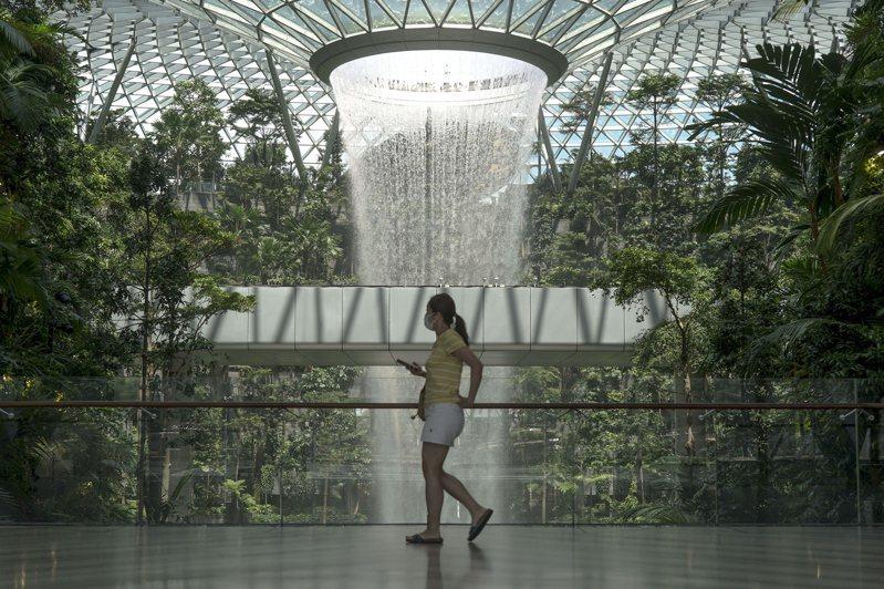 專家認為至少要有七八成人口完成疫苗接種,日常生活才會比較穩定。圖為新加坡樟宜機場內的商場「星耀樟宜」14日重新開放,一名女子經過全球最高室內瀑布「雨漩渦」。(歐新社)