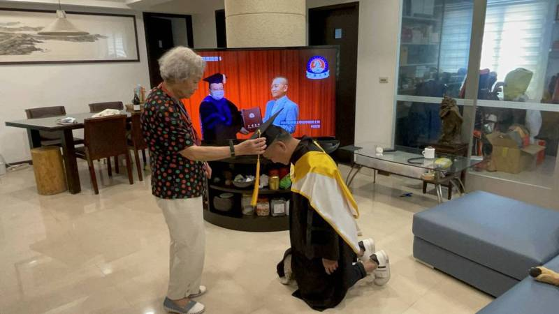 為了報答親恩,何啟聖雙膝下跪,由九十歲高齡的母親為他撥穗。(照片提供:何啟聖臉書)