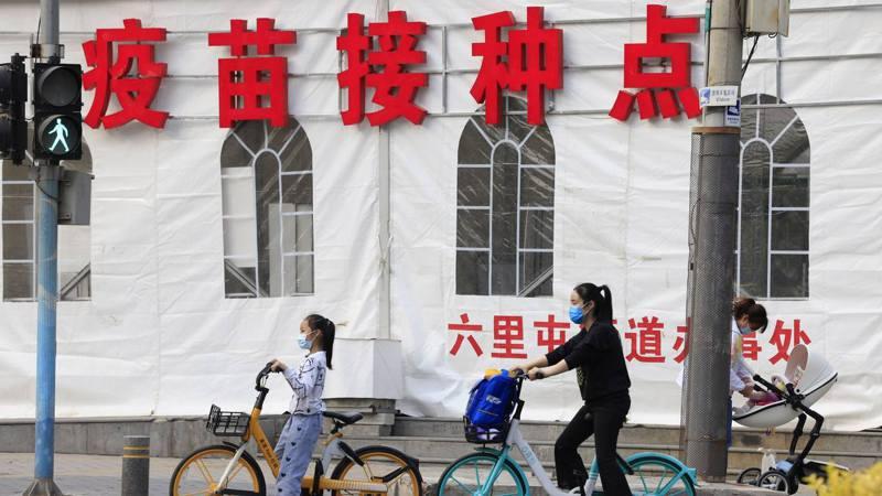 北京民眾經過當地一間疫苗接種中心。 美聯社