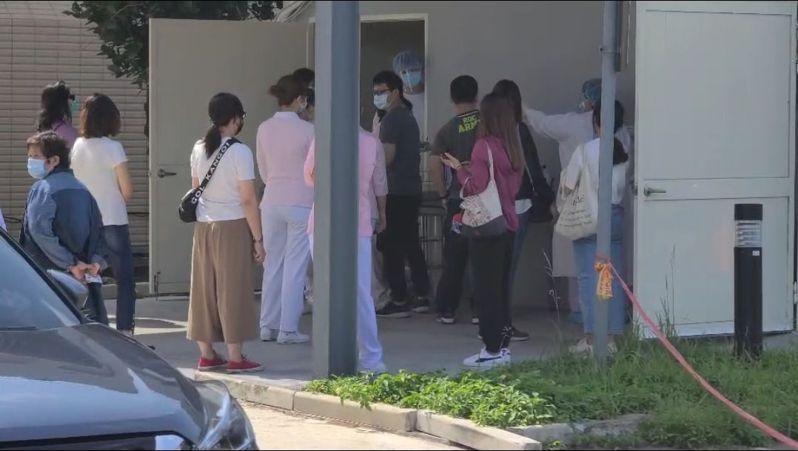 國軍桃園總醫院門診、急診全面暫停,正在進行消毒工作,醫院急診部大樓前,大批醫護正在進行篩檢。記者朱冠諭/攝影