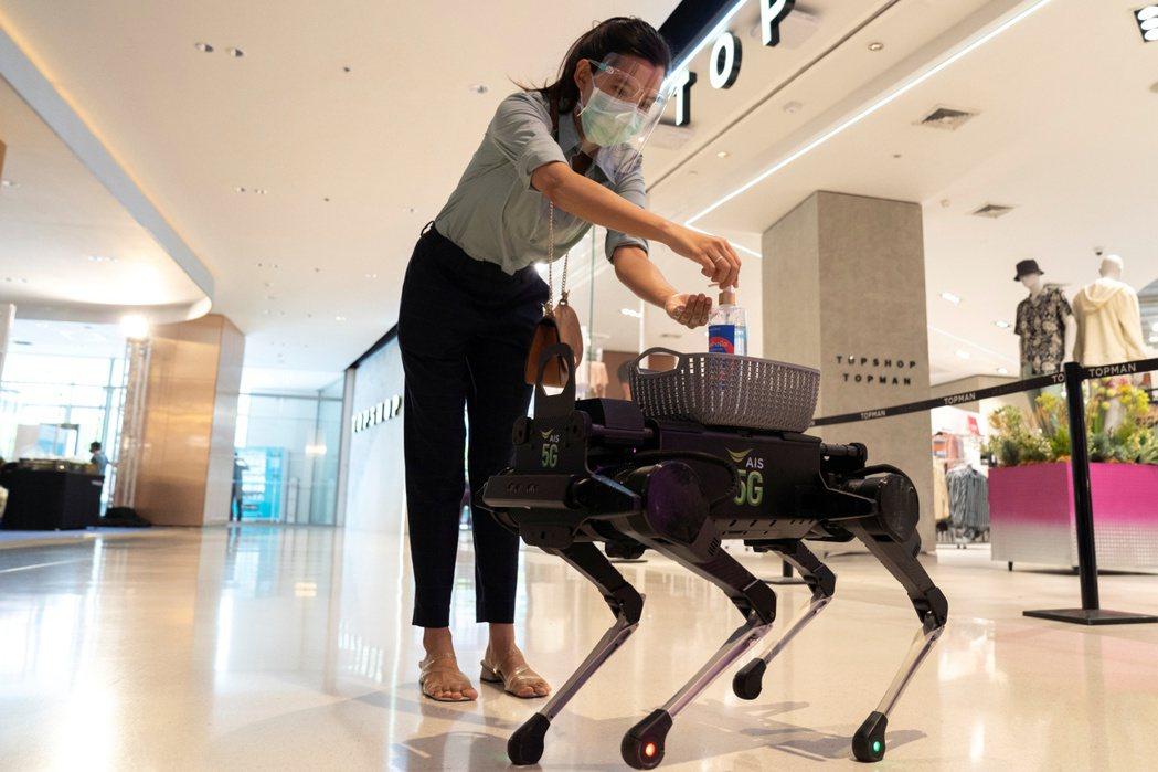 曼谷一家百貨公司用機器狗,為顧客提供手部消毒液。(路透)
