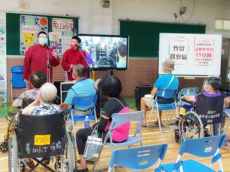 桃園市壽山高中接種站安排藝文團體表演相聲,特別挑選長度約15分鐘的段子,表演結束提醒長輩們離開,有效控制人流。圖/桃園市秘書處提供