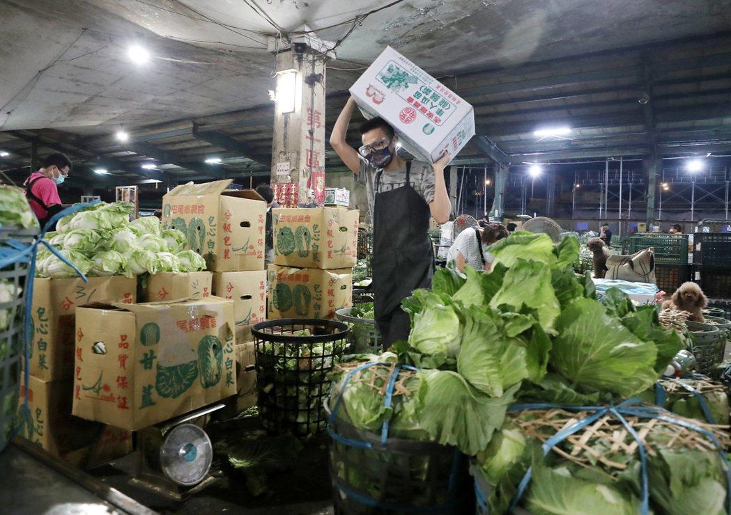 北農負責提供民生必需品,圖為第一果菜批發市場的工作人員,戴著口罩及護目鏡在交易現...