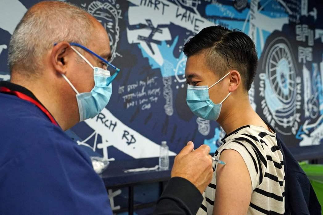 英國將實施新冠疫苗加強劑接種計畫,圖為一位英國民眾20日在托特納姆熱刺隊體育館內...