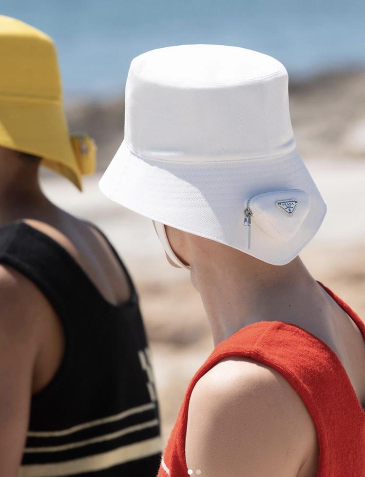標誌性的漁夫帽以前短後長線條呈現,標誌性的PRADA Logo被放在背上或做成帽...