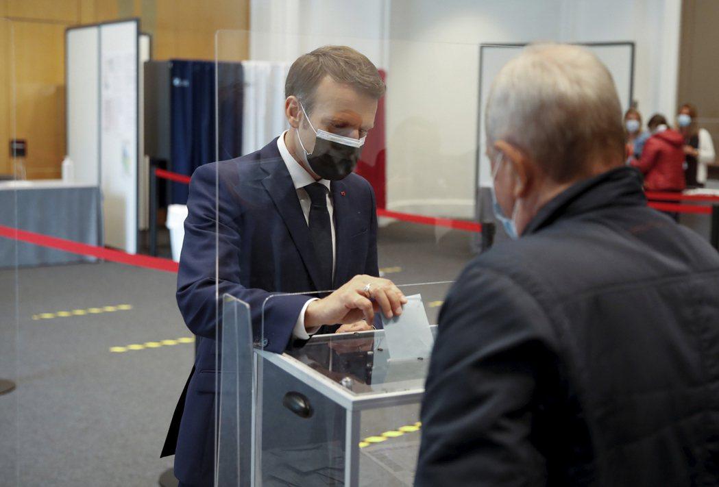 法國總統馬克宏20日在法國北部海濱城市勒圖凱-巴黎-普拉日投票。(美聯社)
