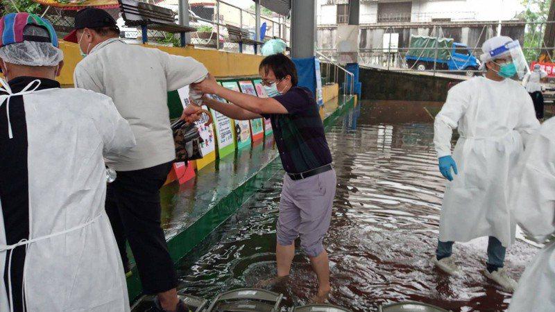 高雄市那瑪夏今天整天雨勢不斷,早上9點設在籃球場的疫苗注射站一度淹水10公分,趕緊換地點轉移到一旁教會。圖/高雄市原民會提供