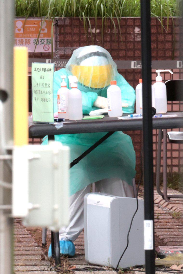 疫情嚴峻,醫護人員工時長、休息不足,一位在快篩站工作的護理師趁著檢驗空檔趴在桌上...