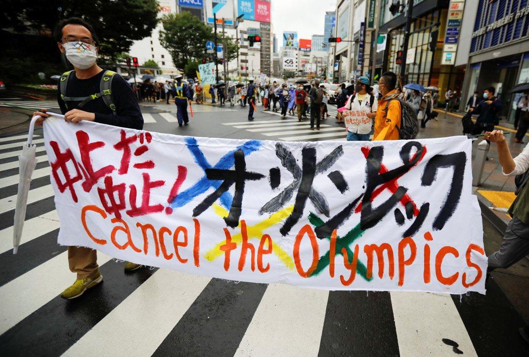 民眾手舉反對東奧的布旗上街抗議。 圖/路透社