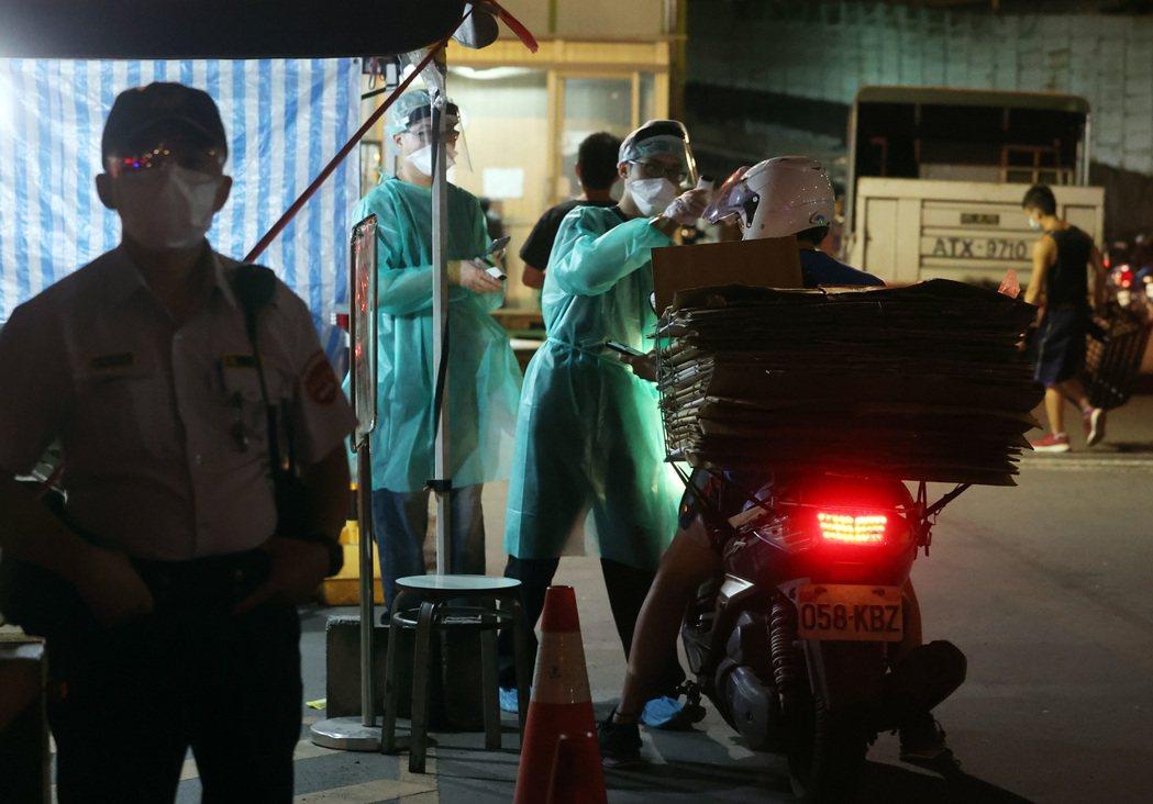台北農產運銷公司爆發群聚感染確診四十五人,各入口都量測體溫才能進入。記者曾吉松/...