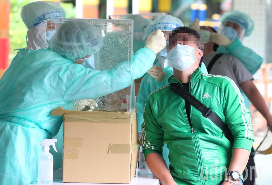 台北農產運銷公司爆發新冠肺炎群聚感染案,台北市政府在萬大國小設置前進指揮所,對拍...