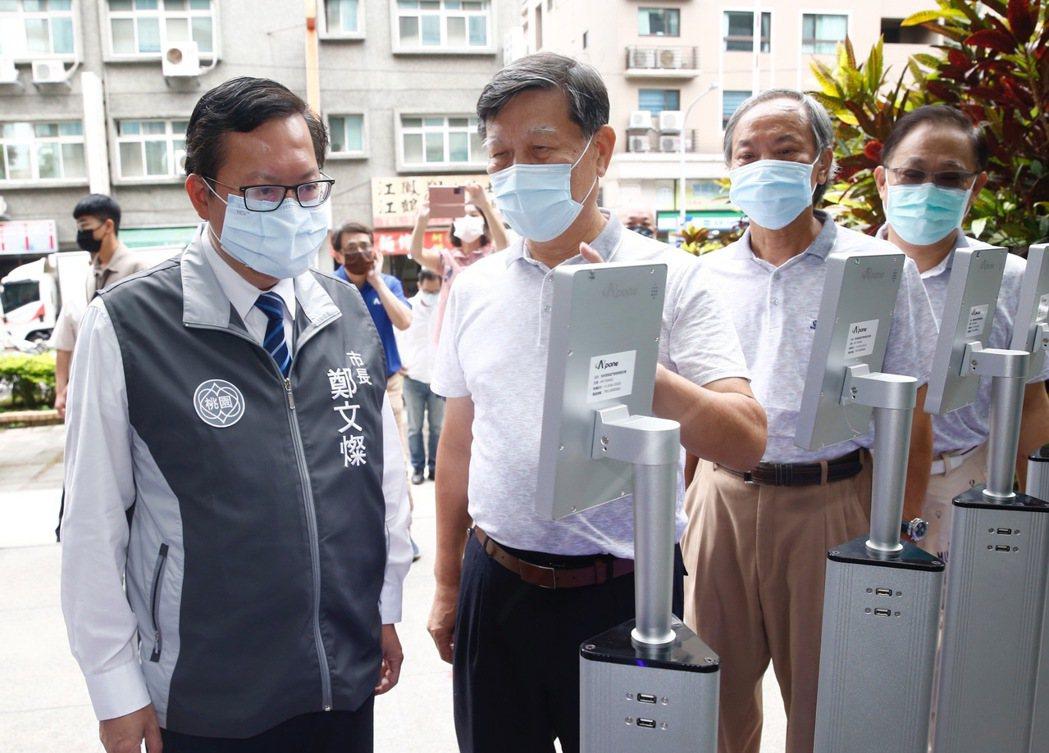 桃園市鄭文燦市長在捐贈單位的解說下使用熱感應測溫機。 崇鼎科技/提供