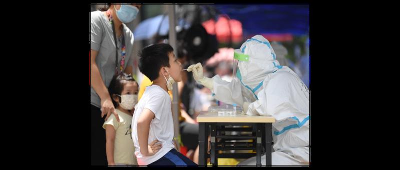 圖為6月12日,廣州荔灣區醫護人員為社區民眾進行核酸檢測採樣。圖/新華社