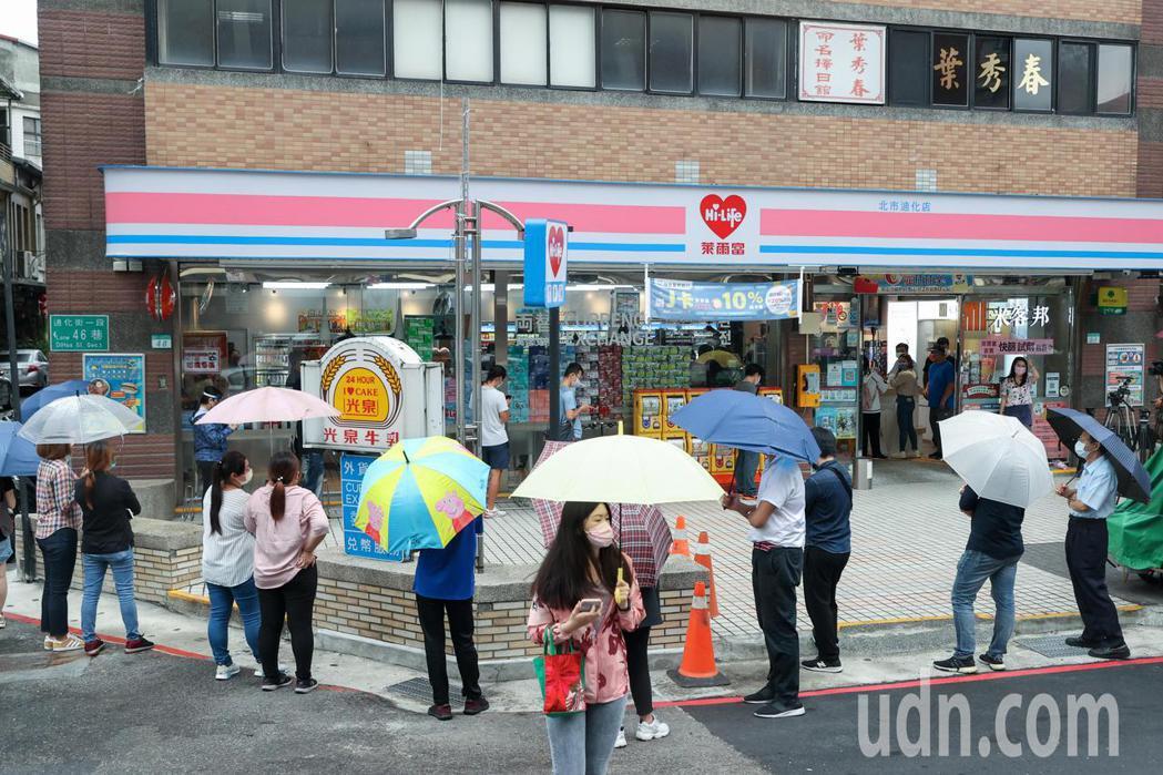 台廠自行開發的快速檢驗套組在萊爾富開賣,即便下雨,開賣前便已有民眾撐傘排隊。記者...