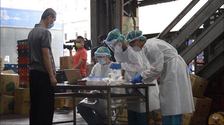 台中榮總醫療團隊今天上午進駐台中果菜市場,為市場攤商快篩,檢驗結果全數為陰性。圖...