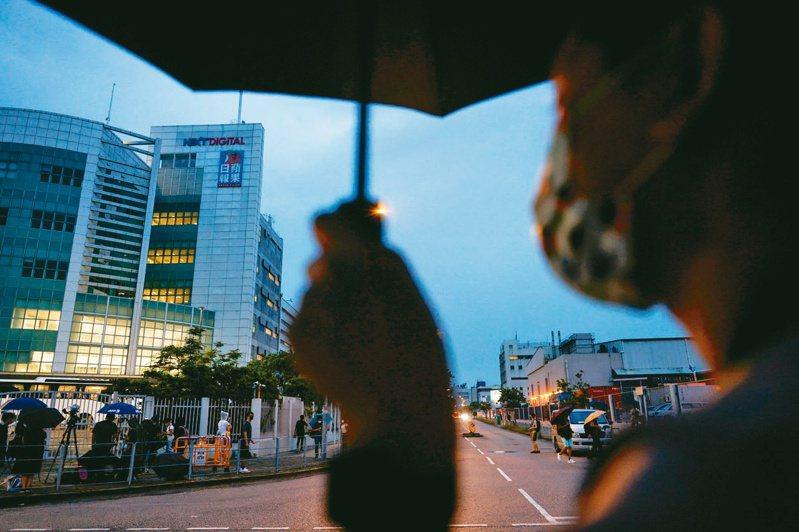 香港蘋果日報今出版最後一期報紙。圖為拿著傘的路人在夜幕中走過蘋果日報大樓前,見證其最後一夜。(路透)