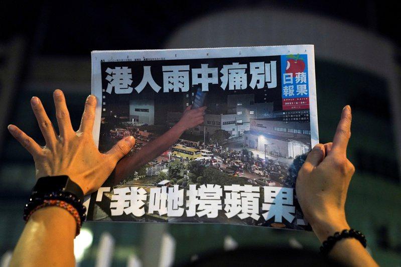 香港蘋果日報終版,一名支持者在2021年6月24日《蘋果日報》最後一期做手勢。 路透社
