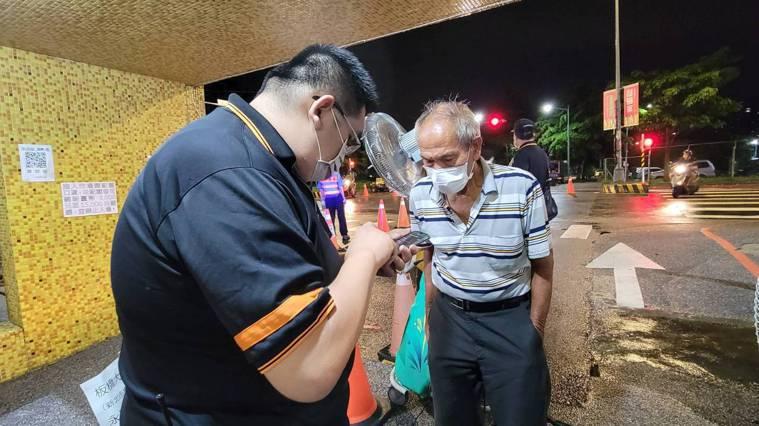 新北果菜公司員工在板橋果菜市場門口為民眾操作手機找篩檢證明紀錄。記者江婉儀/攝影