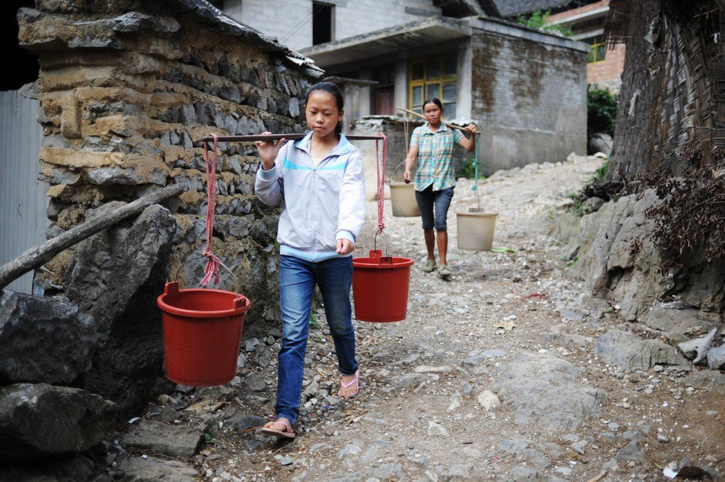 貴州黔南惠水縣龍井村,兩名女子挑著水桶去接水。圖/新華社