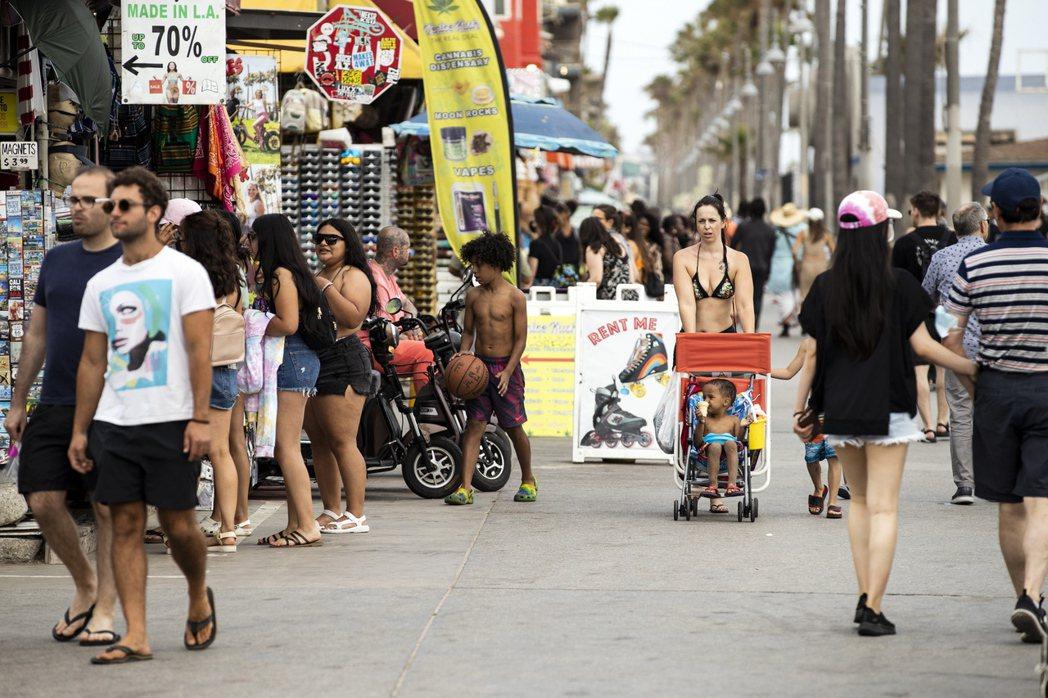 美國加州已解除防疫限制,民眾不戴口罩在海邊逛街。  歐新社