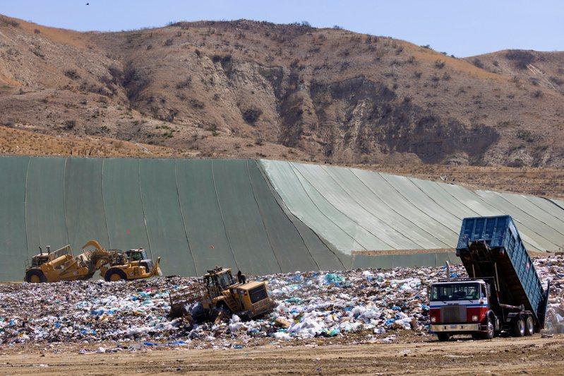美國加州爾灣一個垃圾掩埋場的工作人員用重型機具搬運垃圾。路透