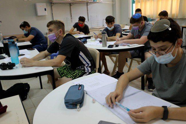 面對新一波疫情來襲,以色列中學生24日在教室上課時,都戴上口罩。  新華社