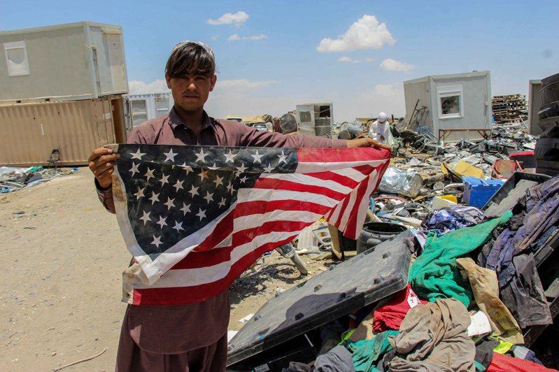 美國自阿富汗撤軍,固然減輕了中國在西部邊境的壓力,但是撤後的戰略真空,中國填補不了,圖為阿富汗民眾手持美軍撤離後留下的美國國旗。歐新社