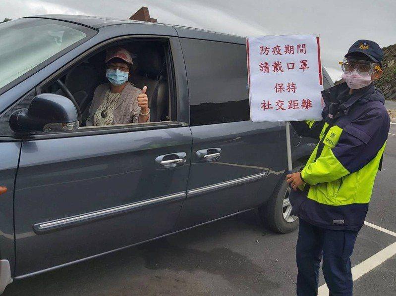合歡山地區近期出現零星遊客,當地仁愛警分局員警舉牌宣導防疫措施,也勸民眾別出門。圖/仁愛警分局提供