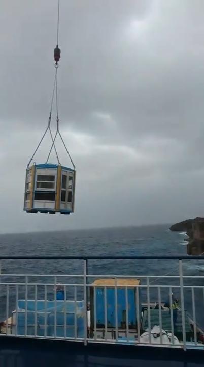 日本大東島因為島嶼四周無法讓船隻靠岸,於是乘客必須裝在一個籠子內,靠吊車懸掛登陸。圖擷取自twitter