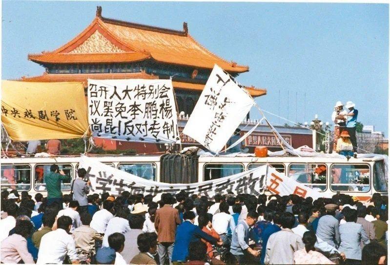 1989年六四天安門事件,北京知識分子在廣場前懸掛反對專制口號、標語。(圖/聯合...