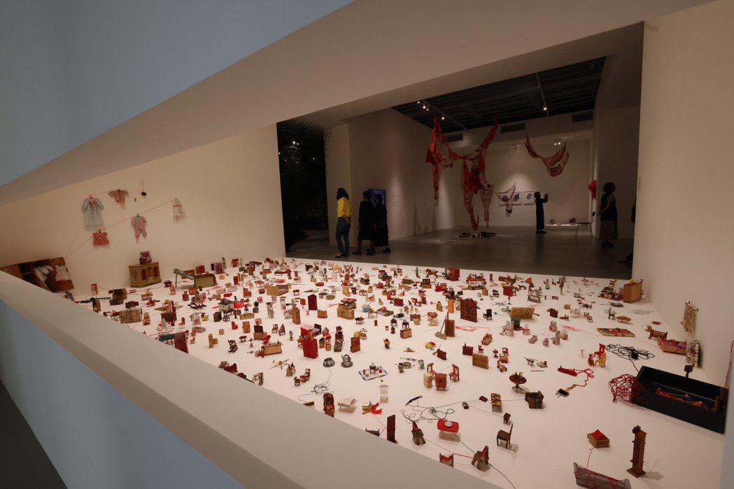 作品《繫著微小記憶》中,塩田千春以紅線連結小娃娃屋的物件,表達出故事性。圖/記者...