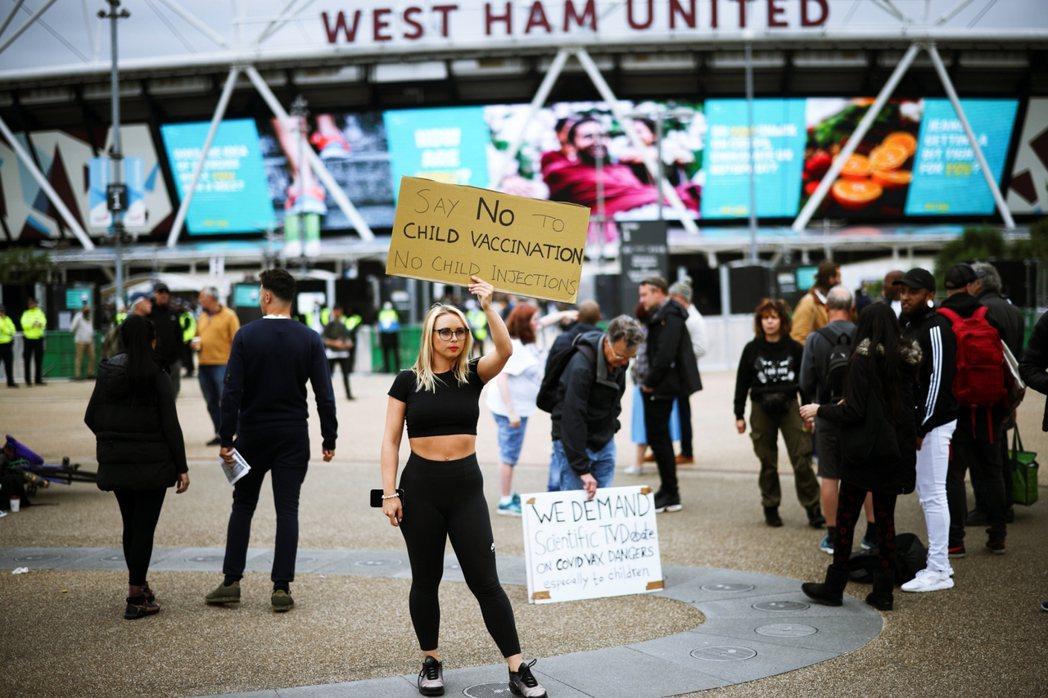 6月19日,東倫敦用於大規模施打疫苗的足球場館外,反疫苗示威者高舉標語「向接種兒...