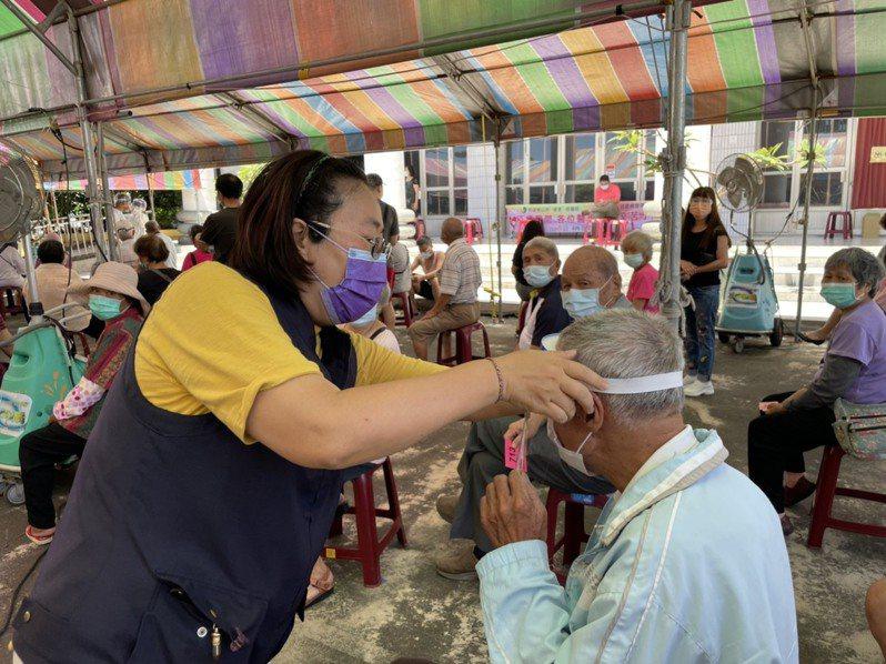 嘉義縣議員林于玲(左)今天至民雄接種站分送防護面罩給長者及家屬。記者莊祖銘/攝影