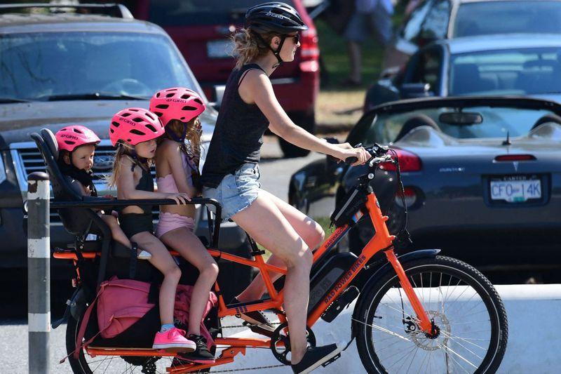 加拿大西部近日遭強烈熱浪侵襲,高溫紀錄不斷被打破,圖為6月29日溫哥華一名婦女載著三名孩子騎著自行車兜風消暑。法新社