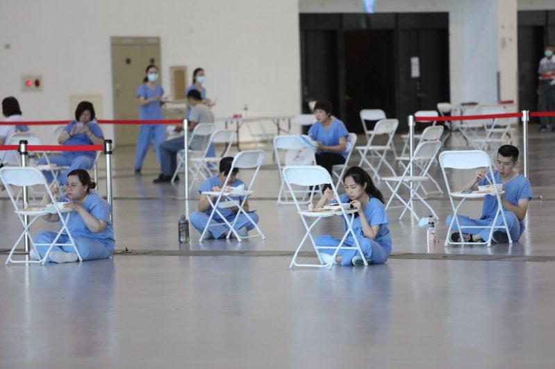 中午休息時間,一群在高雄展覽館施打站的醫護人員席地吃便當,克難畫面引來不少網友心疼喊加油。圖/高雄市府提供