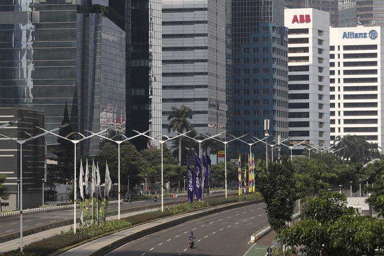 印尼政府實施防疫封鎖,一名摩托車騎士3日在雅加達異常空蕩的商業區道路上騎行。美聯...